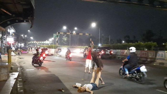 Seorang Pemuda Sedang Menolong Wanita Cantik Yang Berguling-guling di Jalan Raya